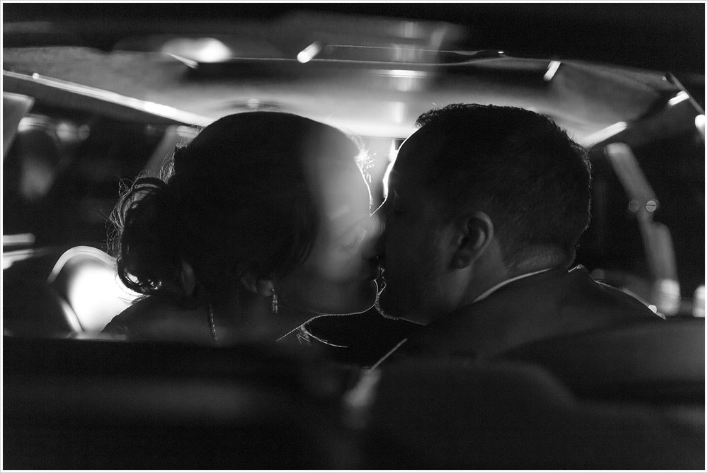 Groom and bride kiss in the back of their limo as they leave their wedding reception - Jason & Melaina Photography - www.jasonandmelaina.com