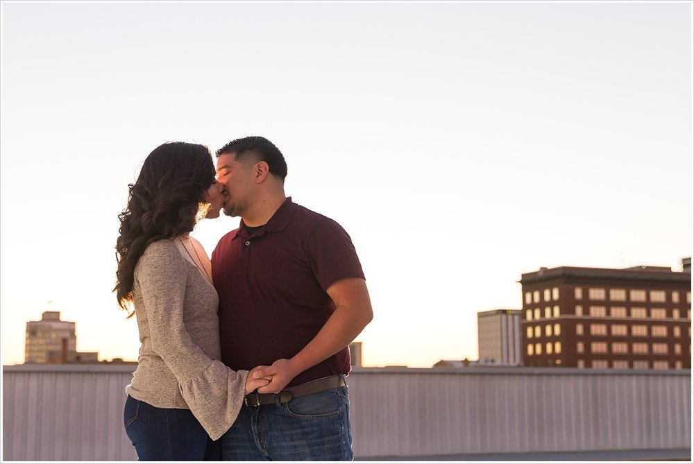A man kisses his fiance on the rooftop of a downtown parking garage at sunset during their engagement photos session in Waco, Texas - Jason & Melaina Photography - www.jasonandmelaina.com