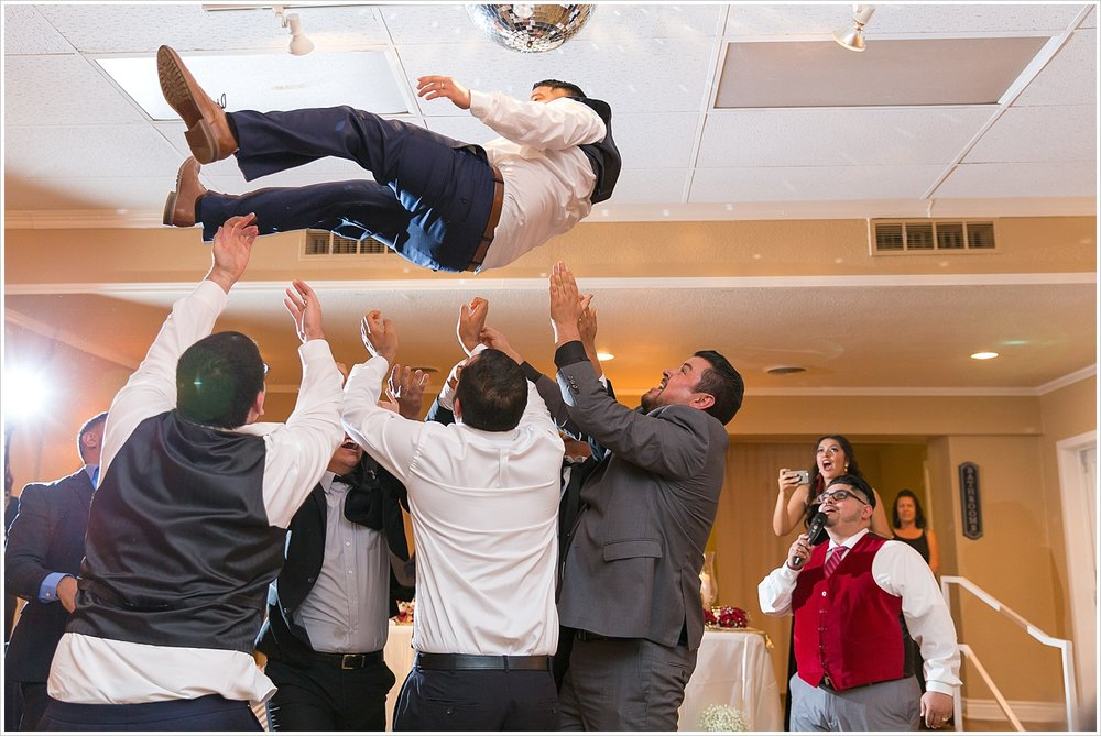 Guests throw the groom into the air on the dance floor during his wedding reception at Castle Heights Bijoux Events Center - Jason & Melaina Photography - www.jasonandmelaina.com