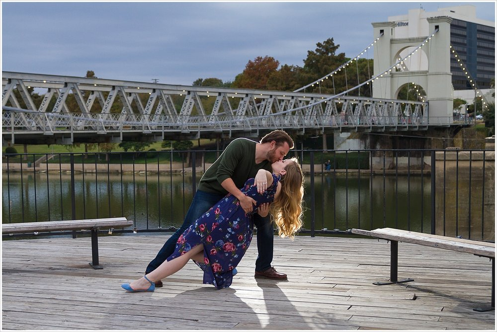 A groom dips his fiance and kisses her during their engagement portrait session near the Suspension Bridge in Waco, Texas - Jason & Melaina Photography - www.jasonandmelaina.com