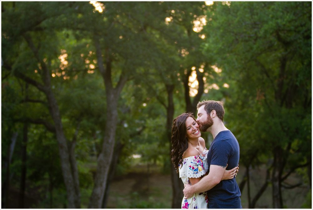 A groom kisses his fiance's cheek during their engagement portrait session in Dallas, Texas - Jason & Melaina Photography - www.jasonandmelaina.com