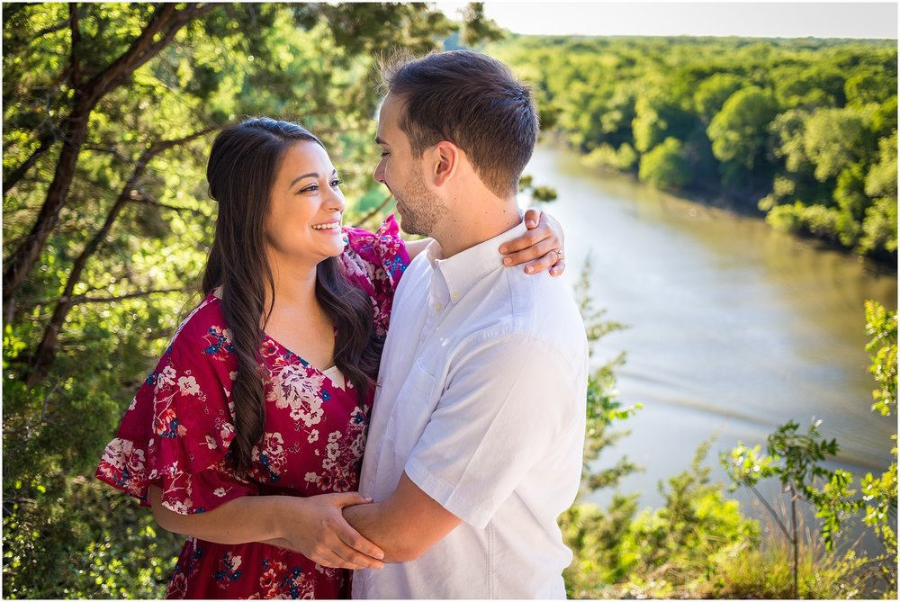 A couple embraces on an overlook of the Bosque River in Cameron Park for their engagement photos - Jason & Melaina Photography in Waco, Texas - www.jasonandmelaina.com