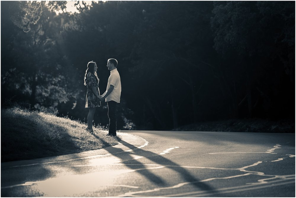 A groom and his fiance hold hands in the sunlight near a road in Cameron Park - Jason & Melaina Photography