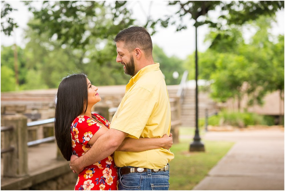 A couple holds one another and looks into each other's eyes during their engagement session in Yettie Polk Park in Belton, Texas