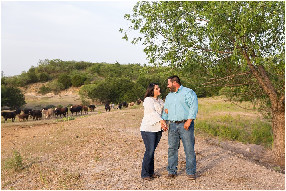 A couple smiles at one another in a field of cows - engagement portraits on a family ranch in Dublin, TX - Jason & Melaina Photography - www.jasonandmelaina.com