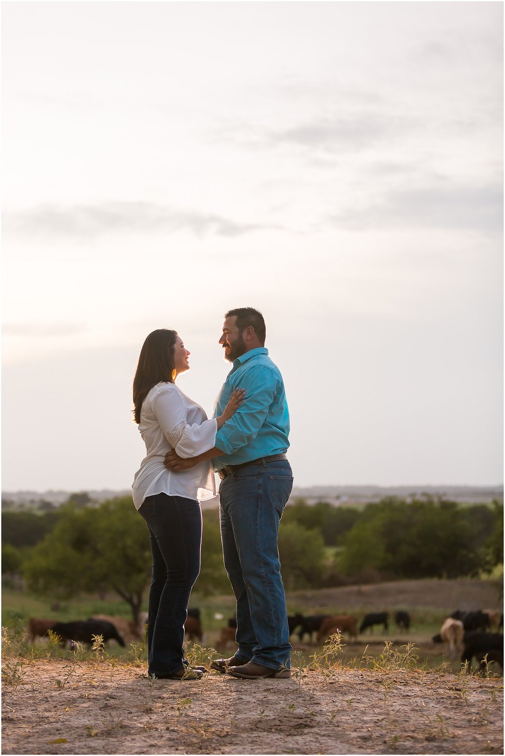 A couple embraces in a field with a Texas sunset behind them during their engagement photos on a family ranch in Dublin, TX - Jason & Melaina Photography - www.jasonandmelaina.com