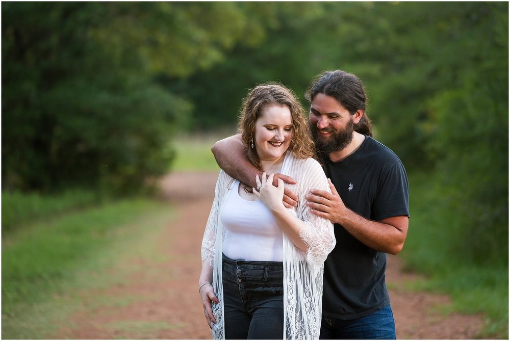 A man hugs his fiance during their engagement session at Lick Creek Park in College Station, Tx - Jason & Melaina Photography - www.jasonandmelaina.com