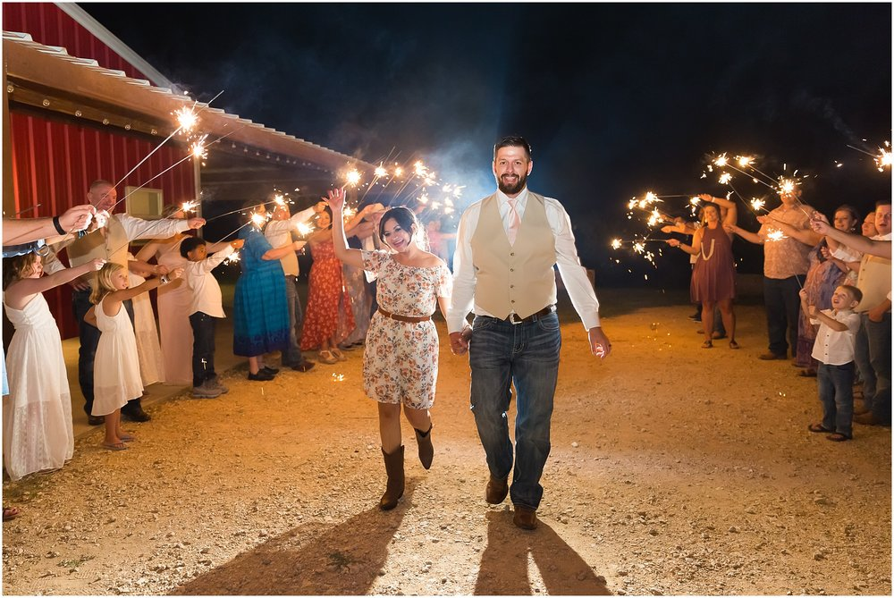 A couple leaves their wedding reception in a sparkler exit Rustic wedding at Rustic Acres in Belton, Texas - Jason & Melaina Photography - www.jasonandmelaina.com