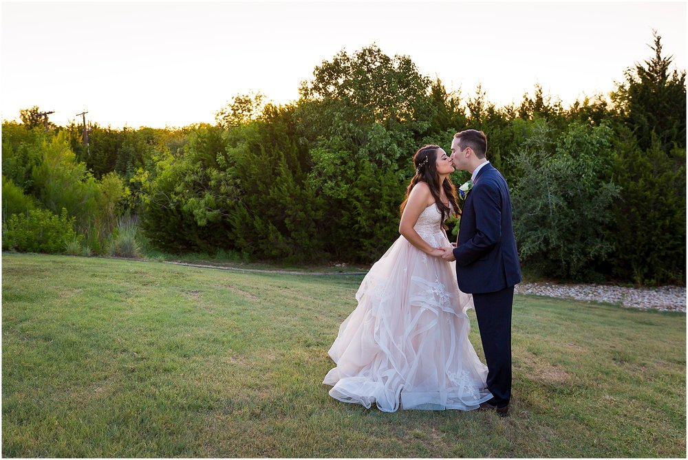 A newly married couple kisses on their wedding day underneath a sunset sky - Jason & Melaina Photography - www.jasonandmelaina.com