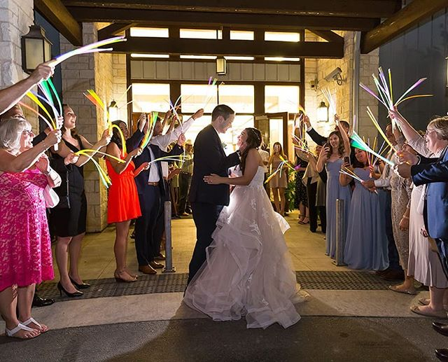 "What do you do when your venue says, ""Nope!"" to your sparkler exit idea, and maybe bubbles aren't your thing?  Dozens and dozens of glow sticks!  Not only are they fun for the exit, but also pretty cool on the dance floor.  And if you have a few leftover afterwards, our two little girls get so excited when we bring a couple home for them the next day. 👨‍👩‍👧‍👧 For a fun #Fridayquestion, what's your favorite wedding reception exit you've seen? What did the couple use?"