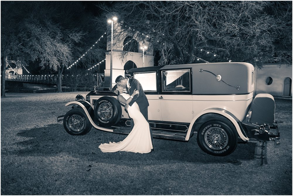 A groom kisses his bride in front of a vintage Rolls Royce after their downtown Waco, Texas wedding at The Hippodrome - Jason & Melaina Photography - www.jasonandmelaina.com
