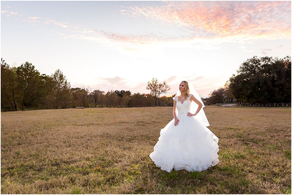Bride poses in a field with a Texas sunset behind her in Salado, Texas - Jason & Melaina Photography - www.jasonandmelaina.com