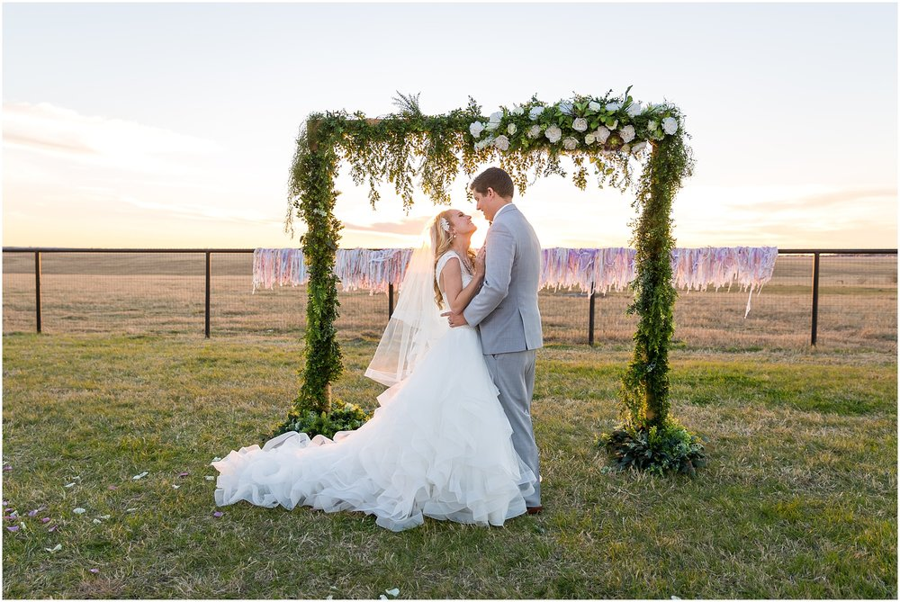 Bride & Groom hold each other as the sun sets behind them - Disney wedding at The Barn at 5 S Ranch - Jason & Melaina Photography - www.jasonandmelaina.com