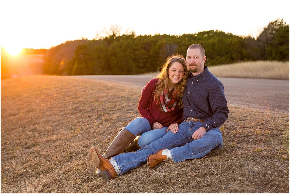 Couple sits beside road with sunset behind them during engagement portraits - Jason & Melaina Photography