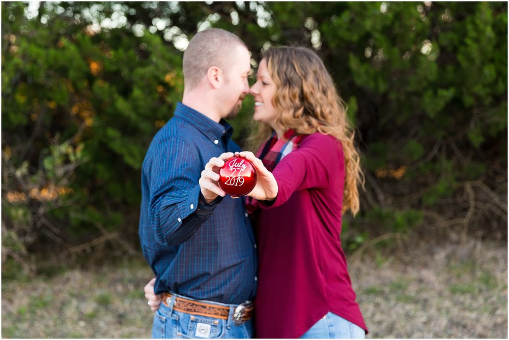 Couple holds Christmas ornament with their wedding date for their save the date - Jason & Melaina Photography