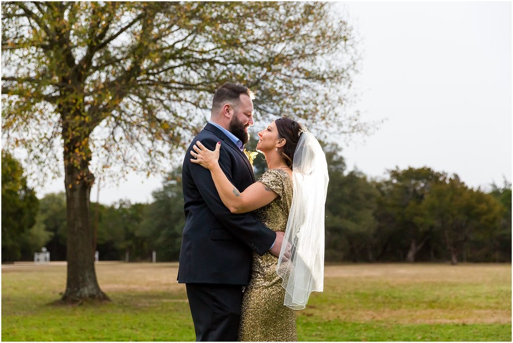 Groom in charcoal suit holds bride in gold sequin dress close to him in the front lawn of a private residence in China Spring, Texas - Jason & Melaina Photography - www.jasonandmelaina.com
