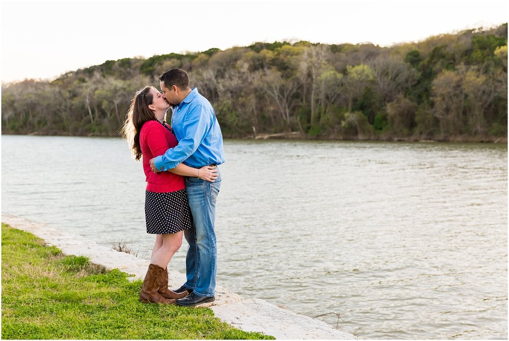 A boy and girl kiss alongside the river and cliffs in Brazos Park East in Waco, Texas during their engagement photo session - Jason & Melaina Photography - www.jasonandmelaina.com