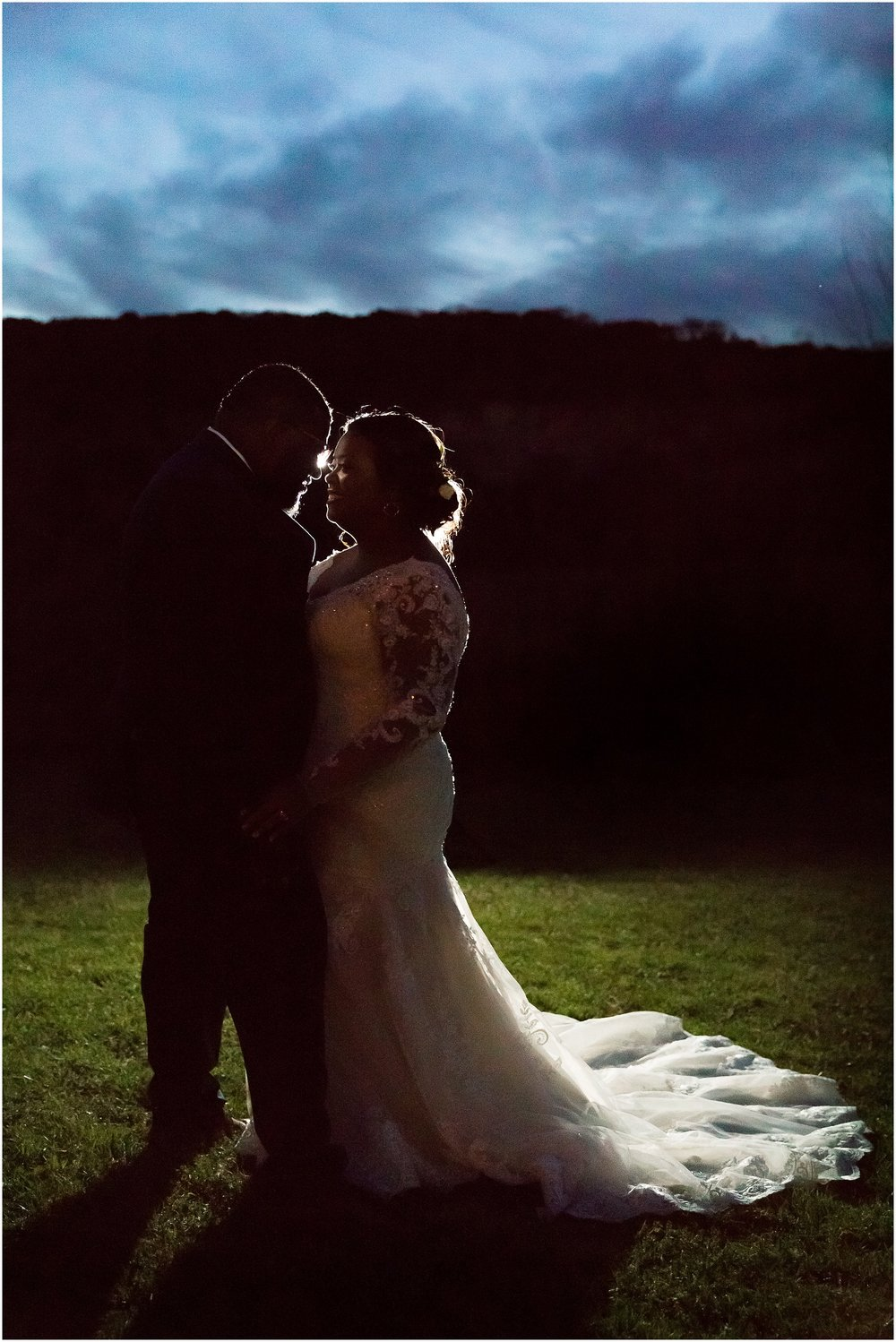 A groom and his bride embrace in the near dark while back lit dramatically with flash in front of the cliffs by the Brazos River in Waco, Texas - Jason & melaina Photography - www.jasonandmelaina.com
