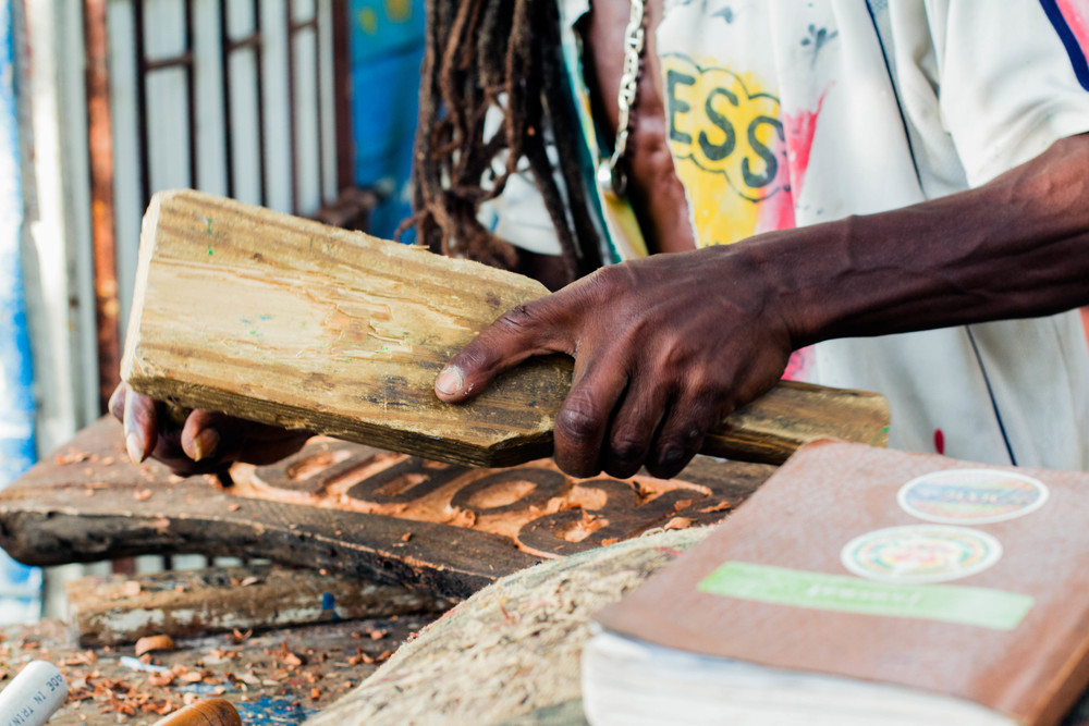 Jah Calo carves a new sign for a friend, October 2015, Ireashia Monét
