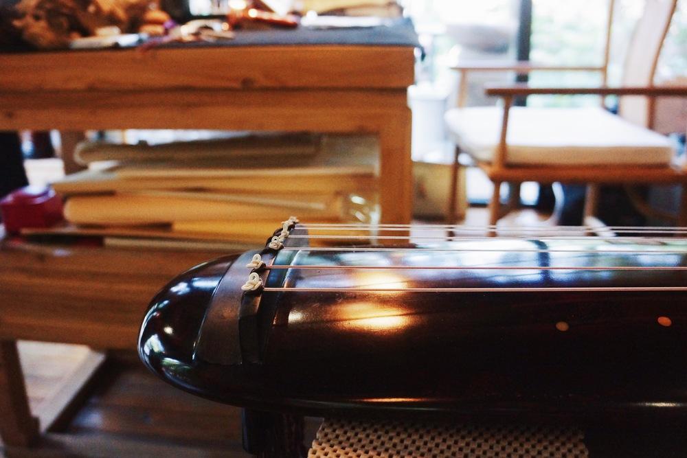 老板的书房,写字弹琴。