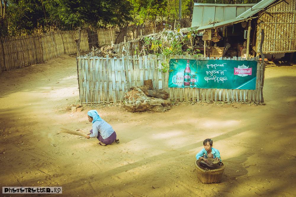 O birmaneză mătură frunzele din praf cu un târn de paie.