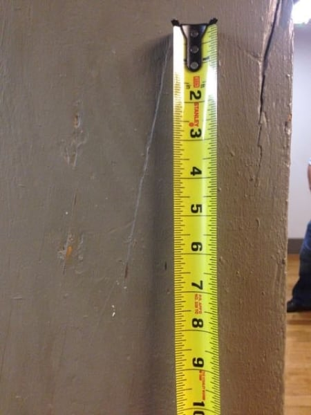 Photo shows painted timber with a depression in the coating that revealed a 1:6 slope of grain as a result of a split. The large split to the right of the ruler was the initial indicator for the presence of slope of grain. Rockefeller Hall. Cornell University, Ithaca, NY.