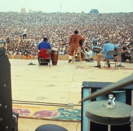 Photo 1 - Richie Havens opening at Woodstock. Stage is constructed with plywood panels that have distinctive paint markings and black triangles.