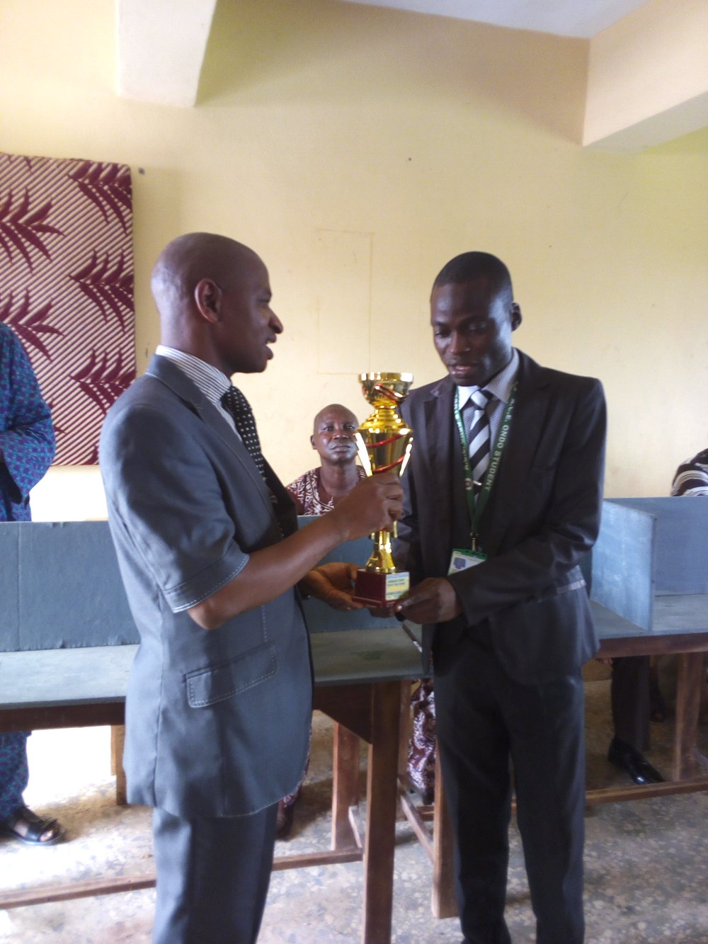 Dr. Kehinde Adenegan presenting the trophy to the winner, Farimoyo Kehinde