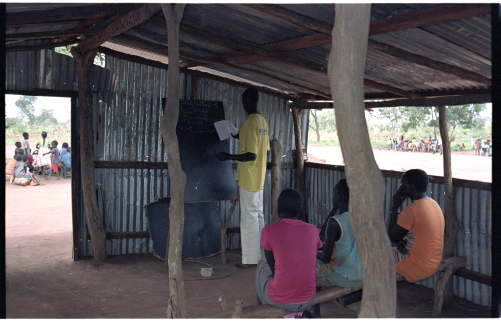 CLASSROOM MADE OF DISCARDED IRON SHEETS AND ITS BEAMS, SMALL TREES.