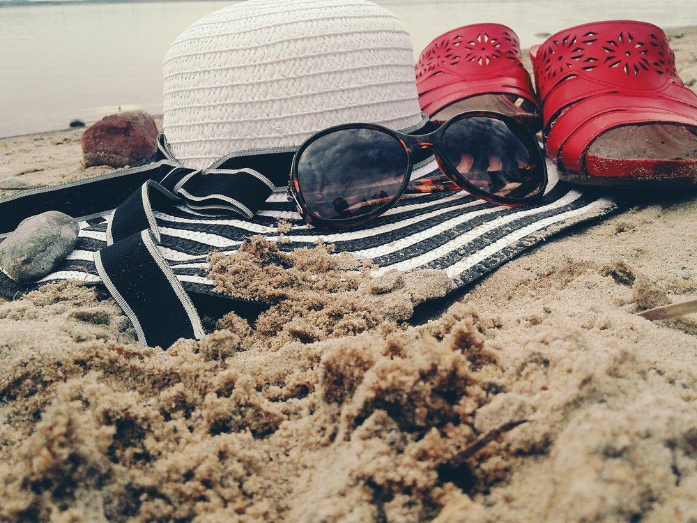 sun hat and sun glasses on a beach