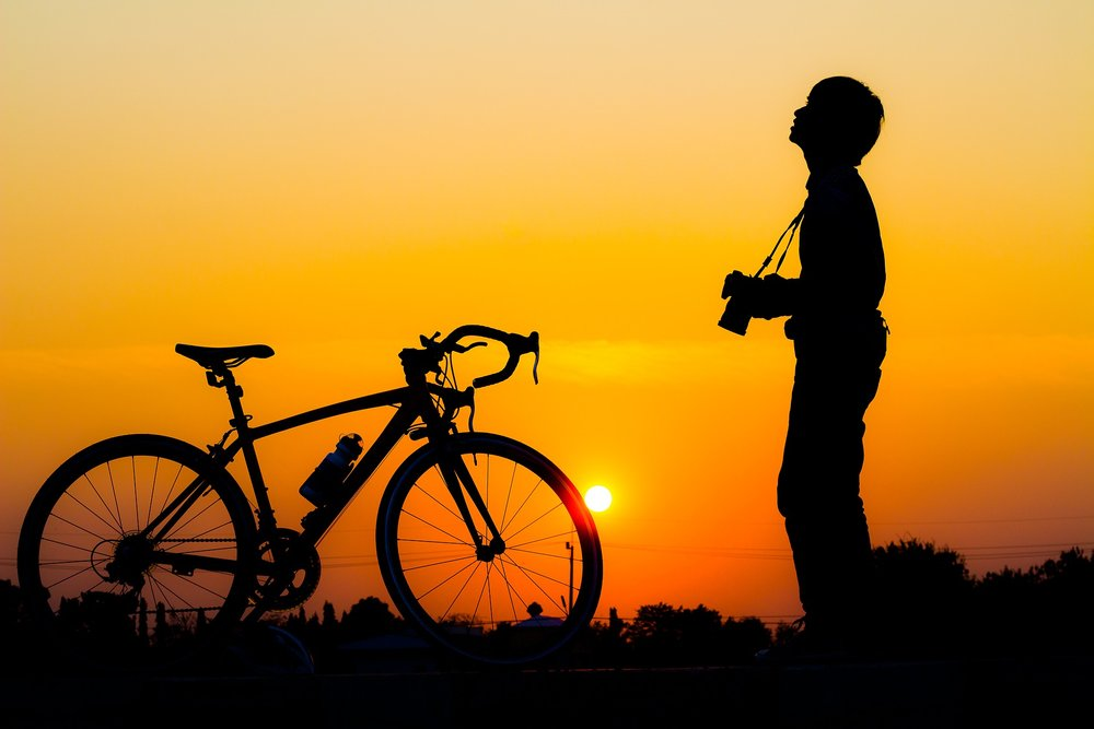 Bicycle and man in front of an orange sunset.