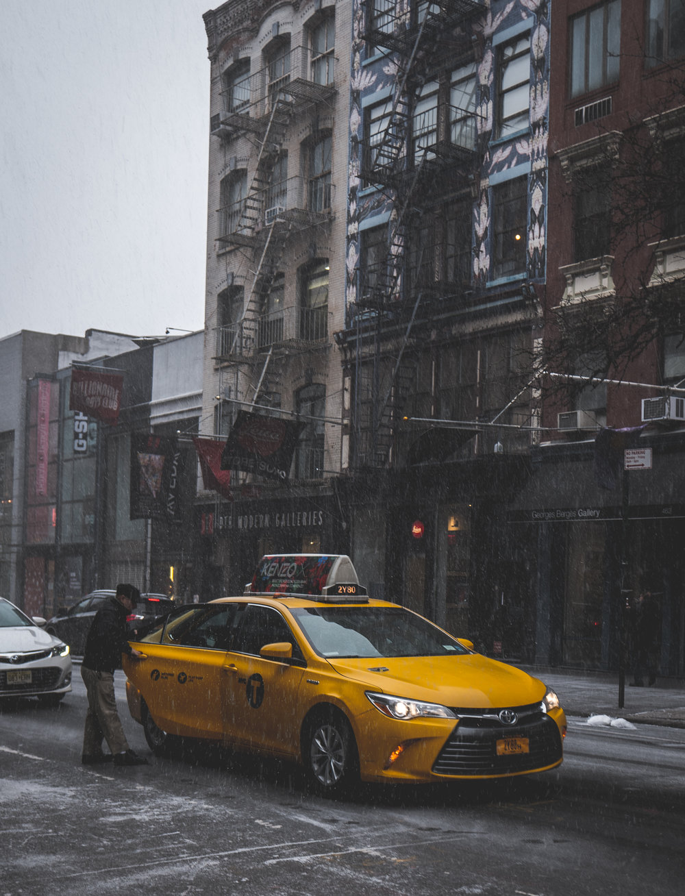 """A classic """"New York"""" photo of man getting into yellow cab. Love the pop of yellow from the cab in this otherwise desaturated dark toned photo."""
