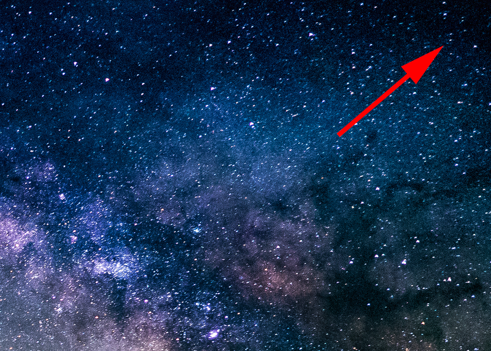 An extreme close up of the top right corner of the photo. The arrow is pointed at no particular star in general just a guide line to show focus on how this lens has barely any to no drop off and distracting aberration.