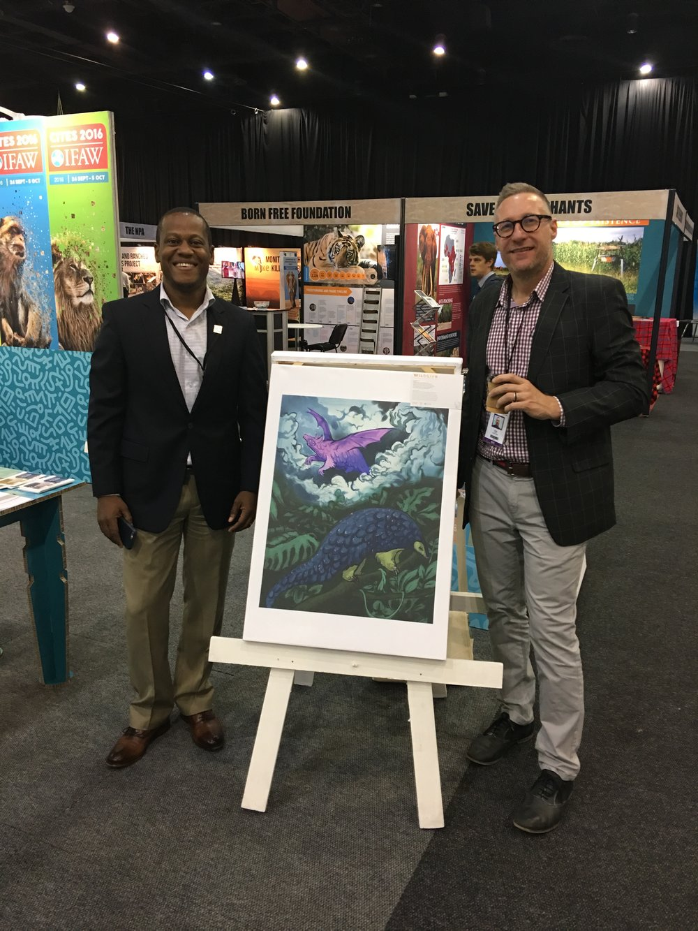 "Kelvin Alie (IFAW Director of Wildlife Trade and Acting VP of Animal Welfare and Conservation) and Jason Bell (IFAW Regional Director of Southern Africa and Elephant Programme) with a canvas print reproduction of ""Demystify"" (pangolins) by Sabrina Mortensen."