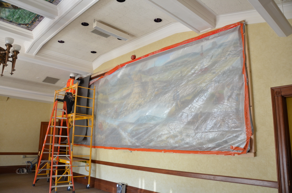 The mural in room 302 is too big to move and is being protected by several layers of plastic, foam and plywood.