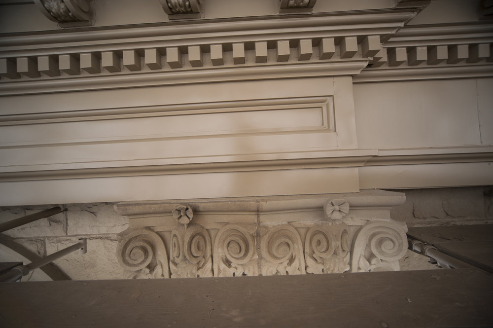 The repaired stone appears lighter in color but will match the rest of the sandstone as it weathers with time. The new entablature is also shown in this picture above the stone.