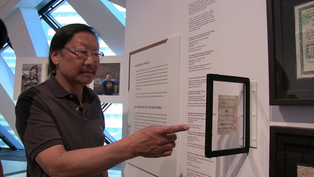 IN INTERVIEW WITH THY PHU, RAYMOND LUM DISCUSSES his father's identification carD used to immigrate from Hong Kong to Vancouver on the Empress of Canada in 1922, which WAS ON DISPLAY AS PART OF  THE FAMILY CAMERA  Exhibition   (ROM, MAY - OCTOBER 2017) (PHOTO: A. MANGAARD, 2017).