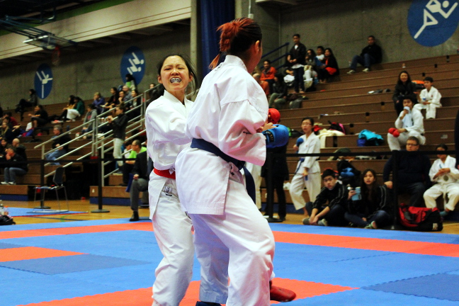 Rita Ngo (red) and Nia Laos-Loo (blue) fought in the women's black belt division. Sparring is usually the first thing that comes to mind when martial arts is mentioned. Photo by Deanna Cheng