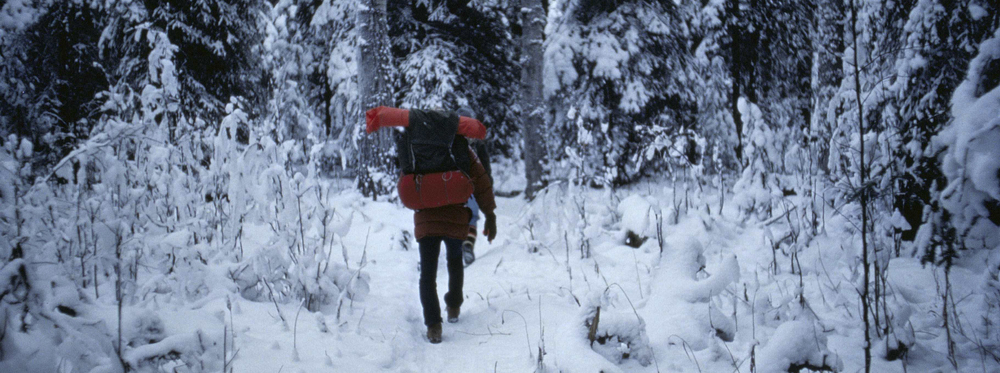 Man_with_backpacking_walking_in_forest_at_winter.jpg