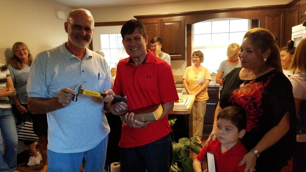 Construction Supervisor Pete Hilty presents the Habitat for Humanity hammer to Homeowners Juan and Johana Lainez