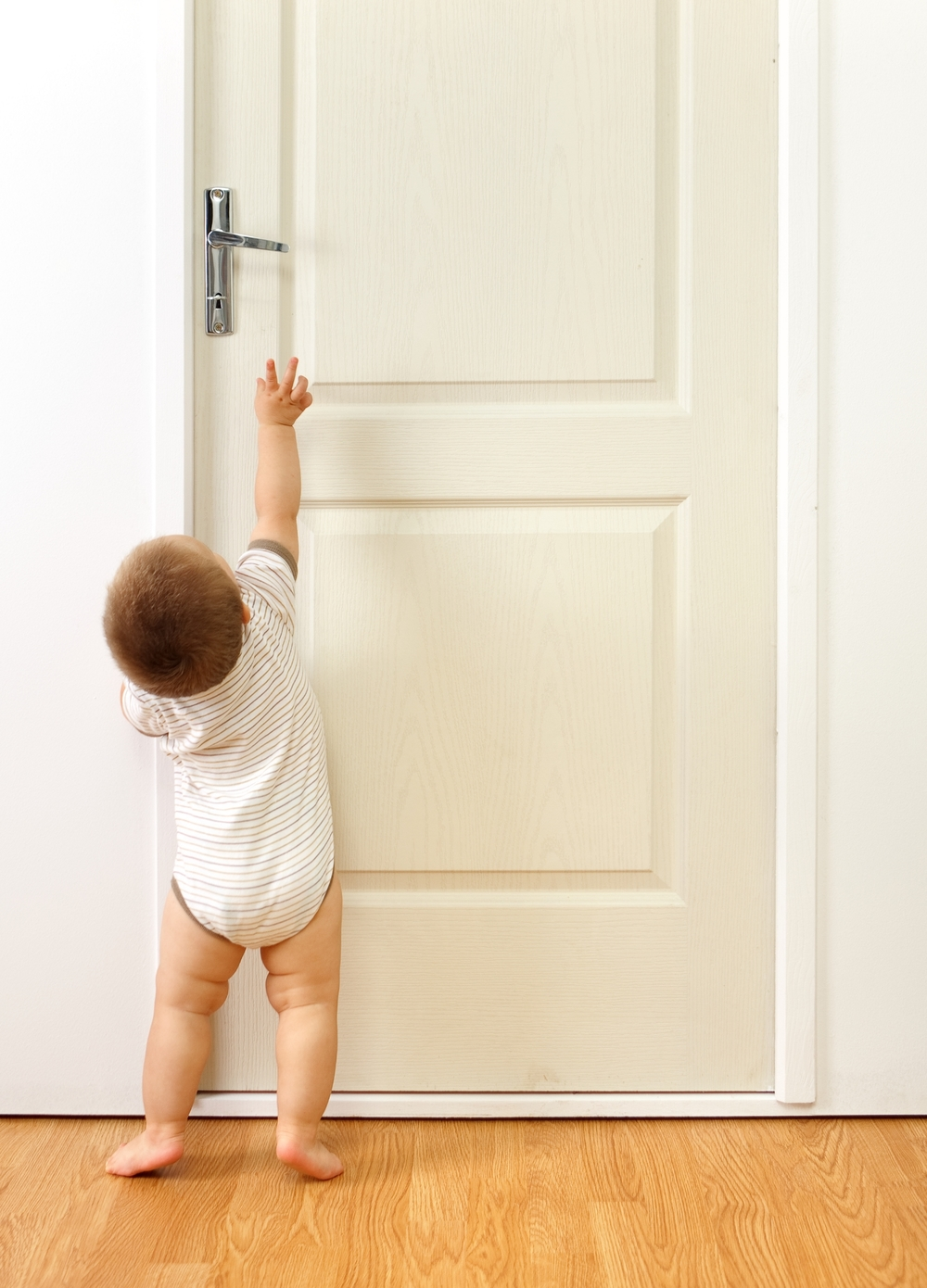 Baby boy reaching for door handle.