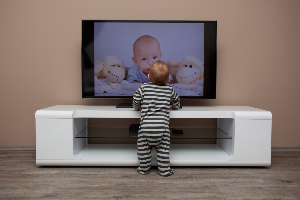Baby standing in front of TV. Reduce tip over risk with anti-tip strap.