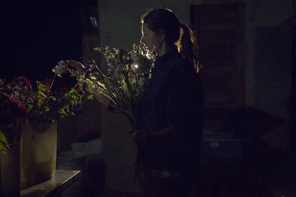 Flower farmer Claire working in the middle of the night making bouquets for a wedding after a day of harvesting on the farm. (British Columbia)