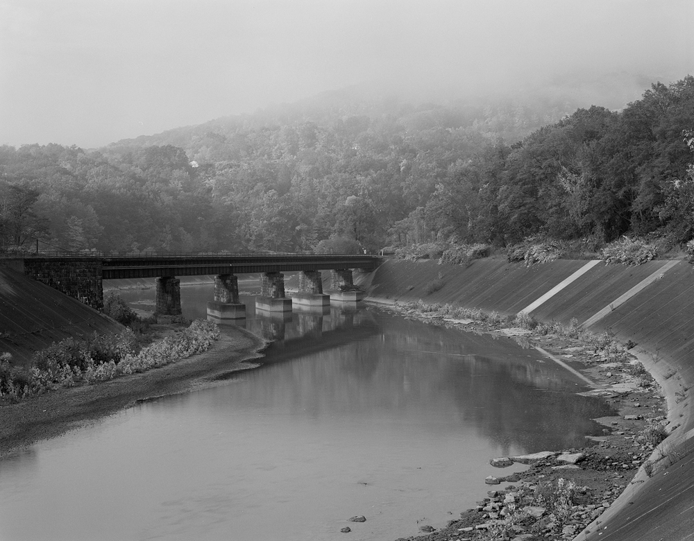 Just west of SG tower near milepost 278 the Sang Hollow Extension crosses the Conemaugh on a ballasted deck bridge at the area know as Dornock Point. Along the ridge in the rear of this image, the mainline continues westward along the southern bank of the Conemaugh River.