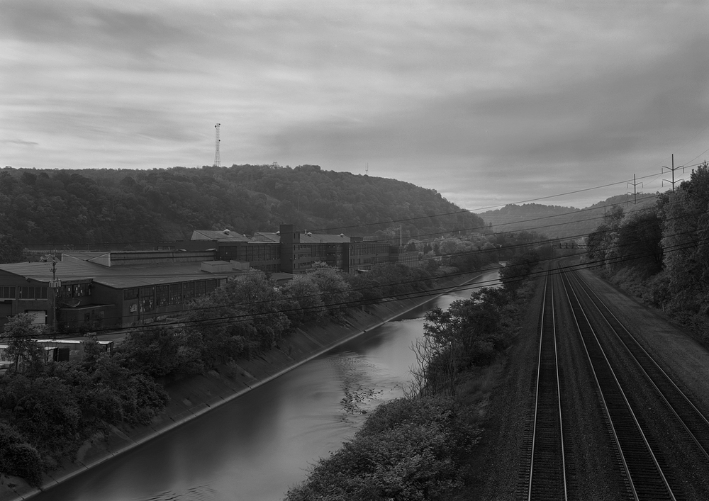 View looking East from Greensburg Avenue. Note the former Westinghouse manufacturing buildings opposite the mainline along Turtle Creek. The home signals at the curve belong to former WG Interlocking, the location of a full interlocking, departure and arrival tracks from the west side of Pitcairn Yard, and divergence of the Port Perry Line to Duquesne, and connection to the Monongahela Line. Today this is Norfolk Southern's Pittsburgh Line, and though greatly simplified both the Main and Port Perry Branch serve as a vital artery to both merchandise, intermodal and mineral traffic through the area.