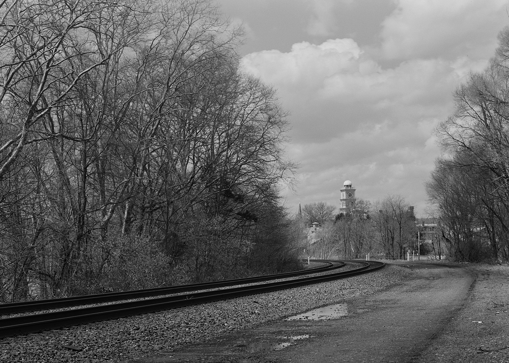The Huntingdon County courthouse tower is visible from the mainline on the sweeping curve entering from the east. Note the access road along the right of way which used to be the alignment of tracks 3 and 4 the former westward freight and passenger tracks respectively.