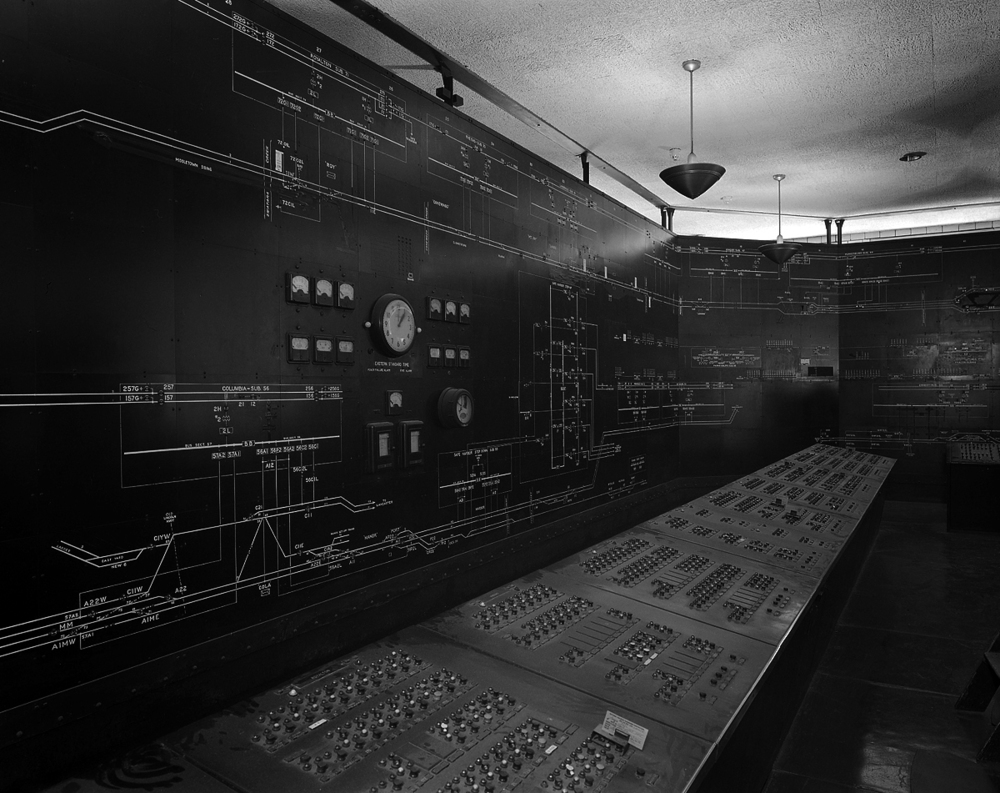 Panel detail of Power Dispatcher's Office in the Harrisburg Passenger Station. This impressive installation dates back to the 1937 electrification to Harrisburg and was responsible for monitoring and controlling electrical loads and supply from Thorndale and Perryville west to Harrisburg. Along the three walls the entire mainline system is illustrated noting substation installations and interlockings, accompanied by indicator lights for the status of both train and signal power. In the foreground are control panels that correspond and essentially functions as breakers for all circuits, phase breaks, and sub stations. This would be a stressful place to work during inclement weather as dispatchers worked against ice, lightning and heavy winds to maintain power to keep trains moving in adverse conditions.