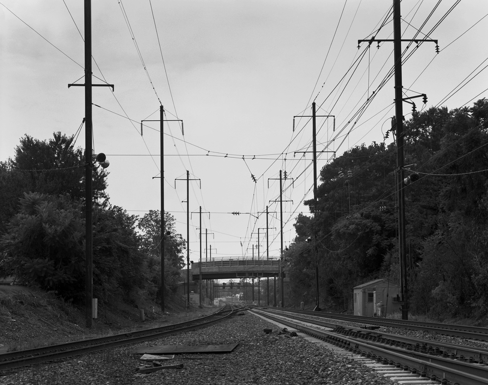 View of current interlocking looking west at Roy. In the distance one can see the eastbound home signals and Amtrak's Middletown station, the overhead bridge is Burd Street. Note the older style relay hut and air plant on the right side of the tracks, this was the site of the original 2 story frame tower that controlled the interlocking prior to the late 1950's project which moved control of this interlocking to State. Norfolk Southern operates the line diverging to the left as the Royalton Branch, which connects to the Enola and Port Road branches at Shocks Mill. This was the former PRR Columbia branch and at one time was a double track electrified artery that linked the mainline with the low-grade line to points east.
