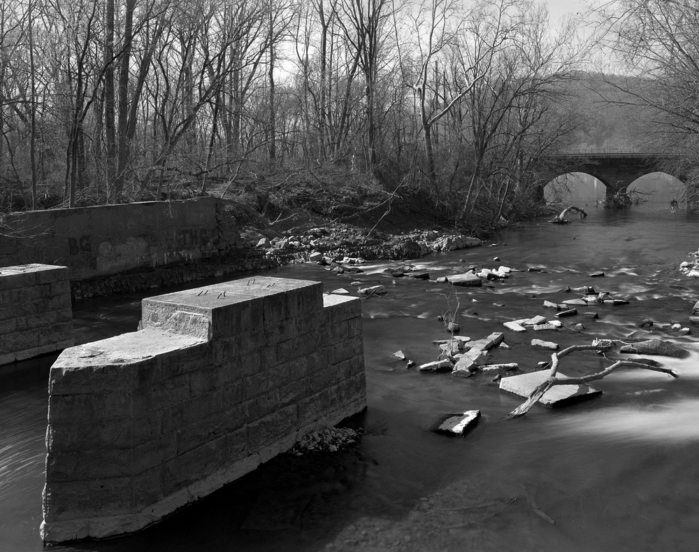 Remaining bridge piers of the former Columbia branch stand up-stream in Chiques Creek. In view is one of William H. Brown's typical stone arch bridges on the active York Have line. This area is located at the former site of the Chickies Furnace, an early site of iron production in the 1800's.