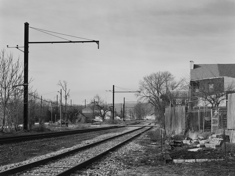 View looking west from the Columbia Branch near the Mill Street crossing. This is the original Philadelphia & Columbia alignment and is operated by NS to access Lancaster area industries and Dillerville Yard, the center of freight operations in the area. Note the steep descent of the branch, compared to the Low Grade visible to the left, which utilized heavier catenary supports on account of it supporting high voltage transmission lines to Royalton. In typical PRR fashion the Columbia branch was maintained to high standards including the use of catenary to provide a relief route in the event there was wreck on neighboring lines.